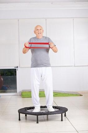 Alter Mann mit Gymnastikband auf Minitrampolin